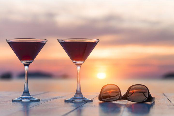 Zweic Cocktails und eine Sonnenbrille vor Sonnenuntergang