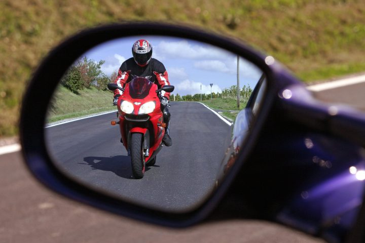 Motorradfahrer nähert sich Autofahrer
