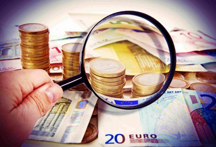 Lupe über Münzen und Geldscheinen