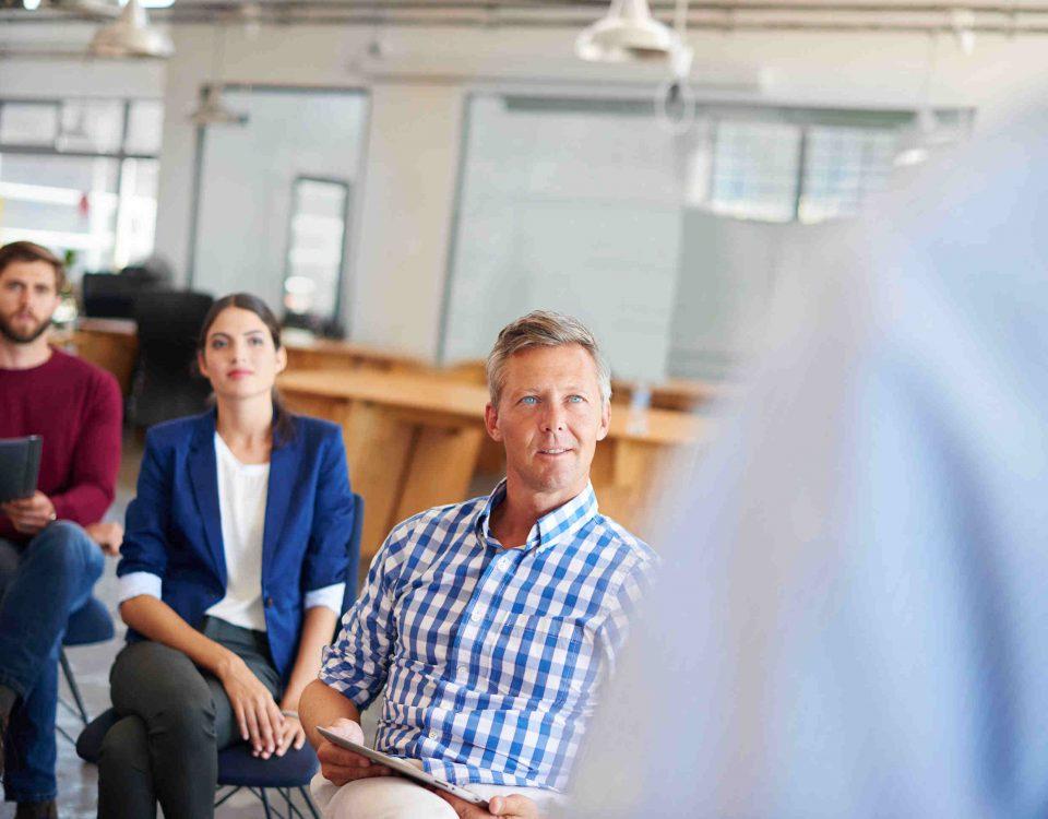Seminarteilnehmer hören Vortragenden aufmerksam zu
