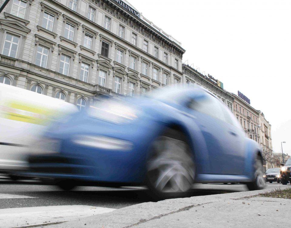 Blaues Auto fährt schnell vorbei