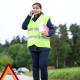 Eine Frau sichert die Unfallstelle ab und setzt den Notruf ab.