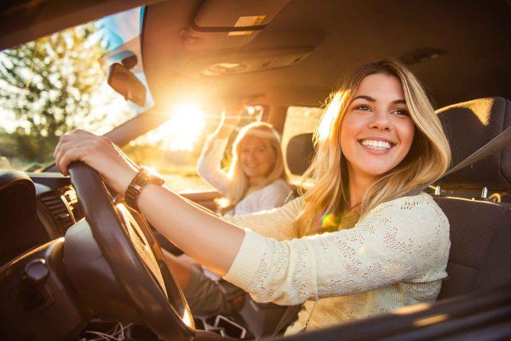 Frau mit Beifahrerin lenkt Pkw und muss Verkehrsregeln beachten