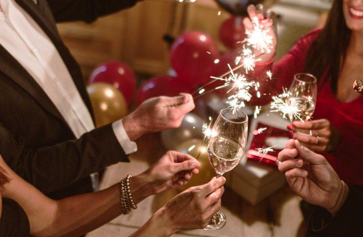 Feiernde stoßen mit einem Glas Sekt und Sprühkerzen auf das neue Jahr an.