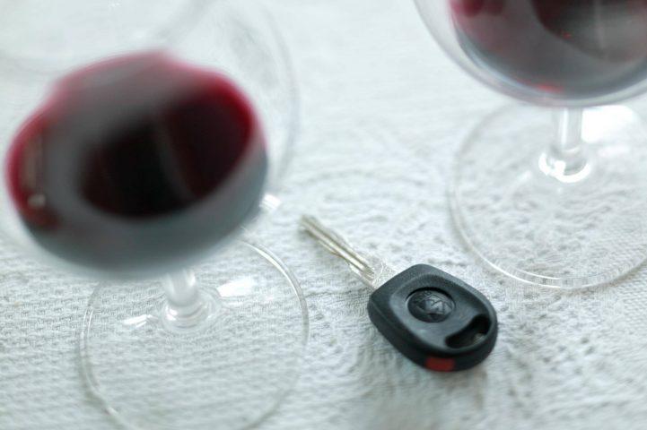 Autoschlüssel neben Gläsern mit Alkohol