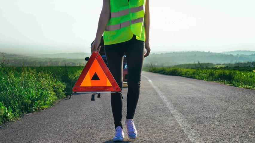 Frau mit Warnweste leistet Erste Hilfe im Straßenverkehr