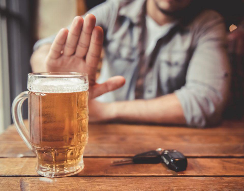 Das Bild zeigt einen Mann, der an einem Tisch sitzt und eine ablehnende Geste Richtung eines vollen Bierglases macht. Vor ihm liegt ein Autoschlüssel.
